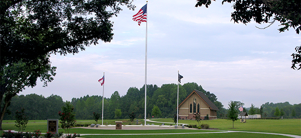 GVMC-Glennville's committal shelter is set on a flat green lawn, with three flag staffs in a gathering area in front.