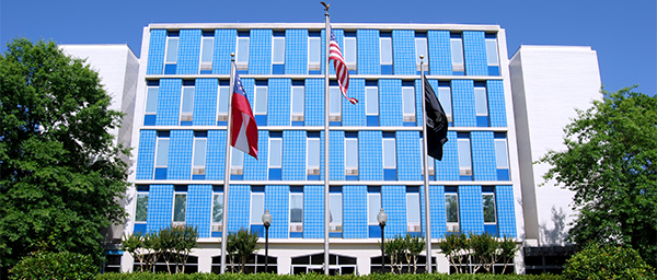 The exterior of the Georgia War Veterans Nursing Home is bright blue, with windows overlooking a plaza with the American, state, and POW flag.